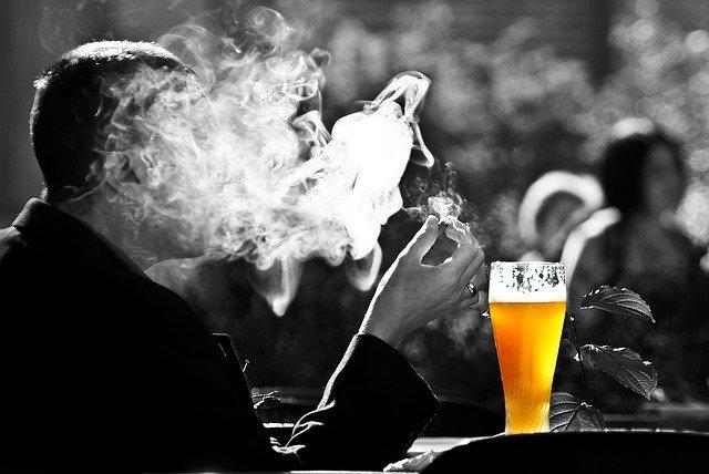 uomo che fuma con birra