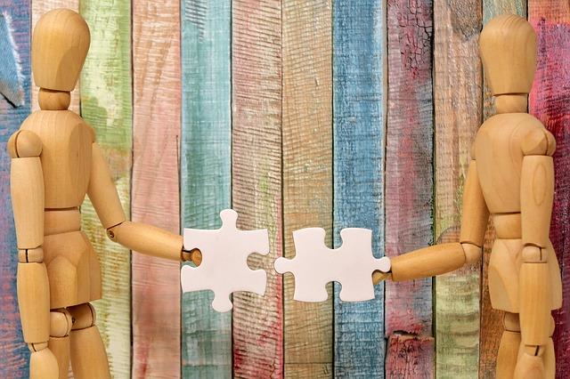 omini di legno con pezzi di puzzle