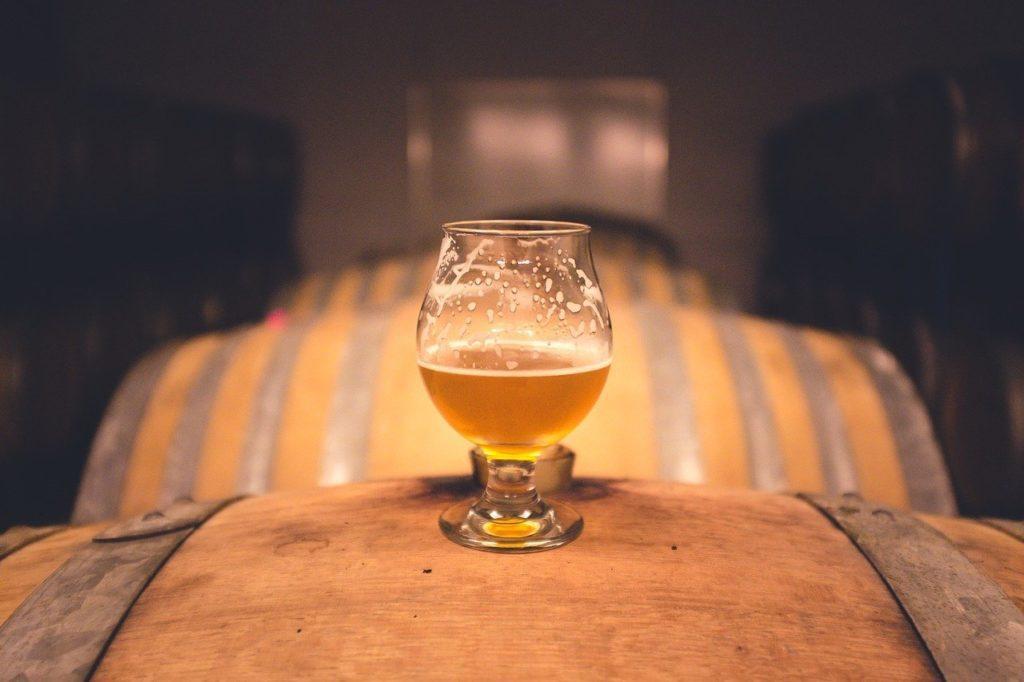 Bicchiere di birra su botte di legno